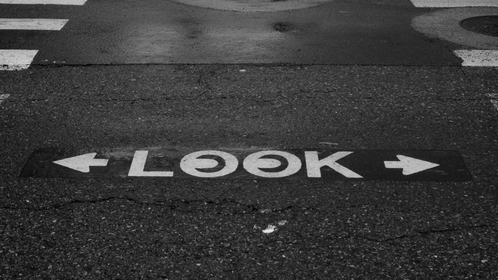 "The word ""LOOK"" painted on a street at a crosswalk"
