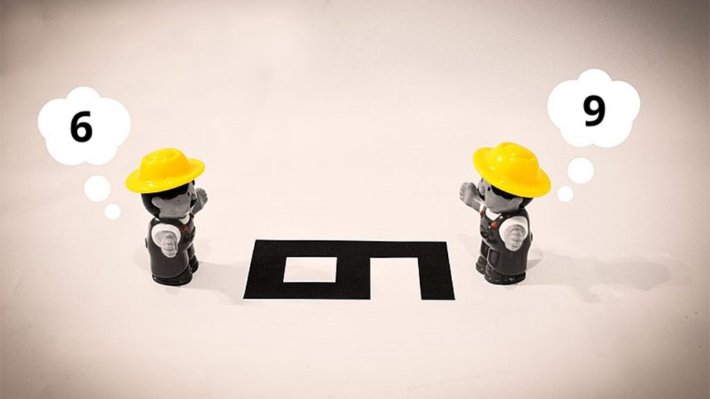 An image of two people describing a number on the ground. To one it looks like a 6, to the other it looks like a 9.